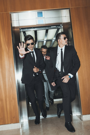 bodyguard obstructing paparazzi when celebrity going out from elevator Stock Photo - 104555581