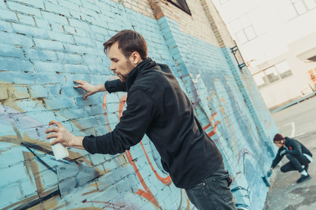 street artists painting colorful graffiti on wall of building