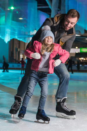 happy father hugging adorable little daughter on skating rink