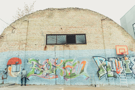 back view of man painting colorful graffiti on wall with basketball hoop and ladders