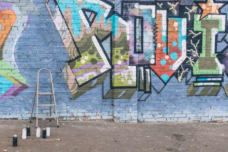 Latas con pintura en aerosol y escalera cerca de coloridos graffiti en la pared del edificio en la ciudad Foto de archivo