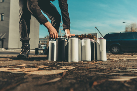 street artist taking cans with colorful spray paint for graffiti