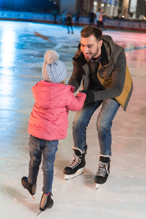 happy father and daughter holding hands and looking at each other on skating rink