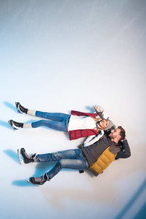 top view of beautiful happy young couple lying together on ice of skating rink