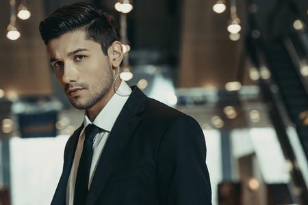 handsome security guard with security earpiece looking away 版權商用圖片