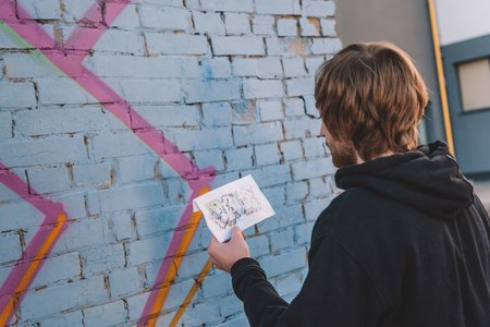 street artist looking at sketch and painting colorful graffiti on wall Reklamní fotografie
