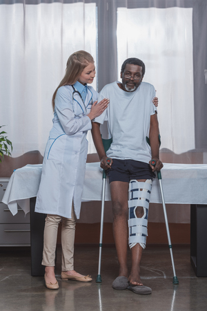 Young doctor helping stand up to african american patient with leg brace and crutches