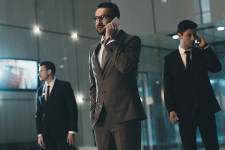 businessman talking by smartphone in business center