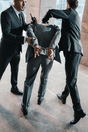 Imagen recortada de guardias de seguridad arrestando al delincuente Foto de archivo