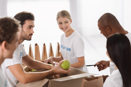 group of young multiethnic volunteers packing food for charity Standard-Bild - 104555976