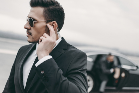 handsome bodyguard of businessman listening message with security earpiece 写真素材