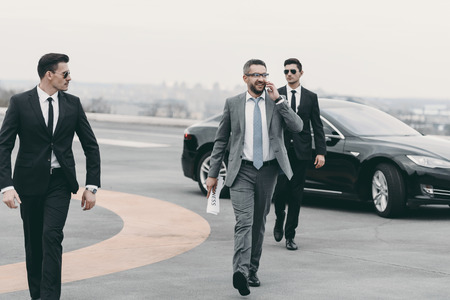 businessman walking with bodyguards on helipad and talking by smartphone Stock Photo