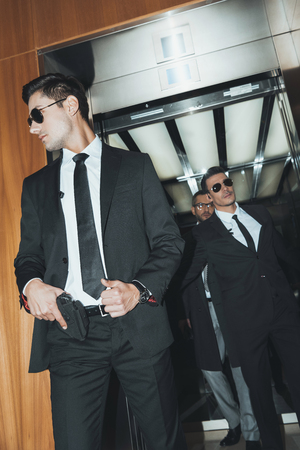 bodyguard putting hand on gun when going out from elevator with politician