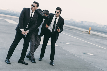 two bodyguards in sunglasses protecting businessman with gun Stock Photo
