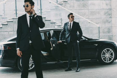 bodyguards in sunglasses standing at car and waiting for politician 版權商用圖片