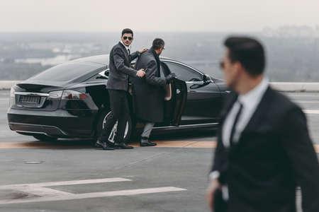 guardia del corpo aiutando uomo d'affari a sedersi in macchina nera