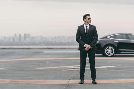 ernsthafter Leibwächter, der mit Sonnenbrille und Sicherheitsohrhörer auf Hubschrauberlandeplatz steht und wegschaut Standard-Bild