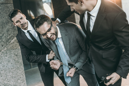 Cropped image of security guards arresting smiling criminal