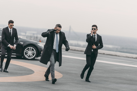 businessman covering his face with hand and walking with bodyguards Stock Photo