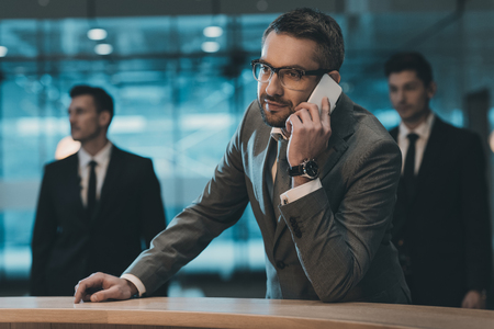 businessman talking by smartphone and standing at reception counter Stock Photo