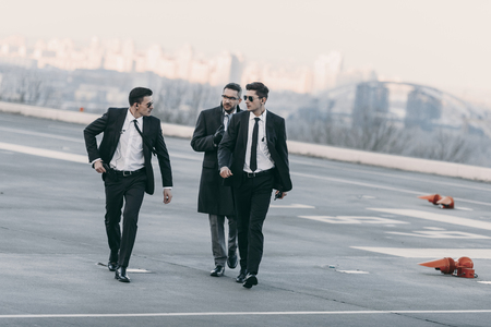 businessman walking with bodyguards in sunglasses and suits on helipad