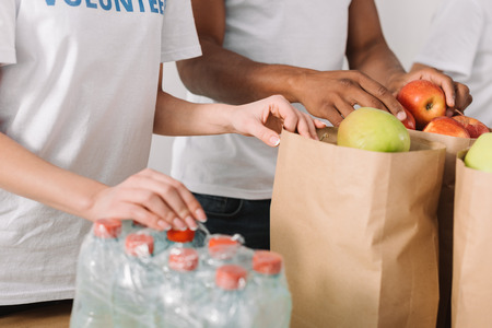 cropped shot of volunteers with apples and water bottles on table Stock Photo