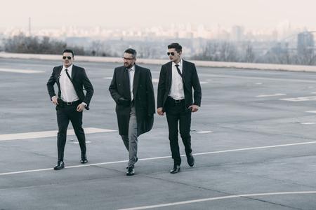 businessman and two bodyguards walking on helipad Stock Photo