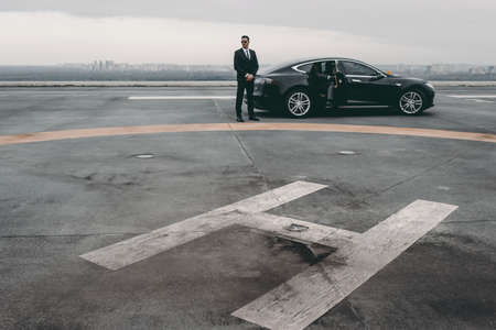 bodyguard standing close to businessman car on helipad