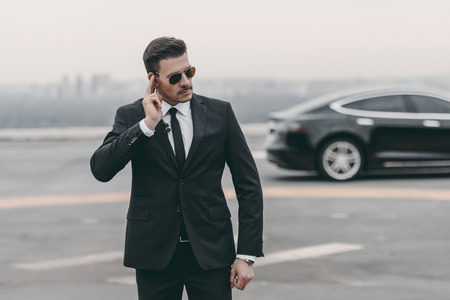 serious bodyguard listening message with security earpiece on helipad Stock Photo