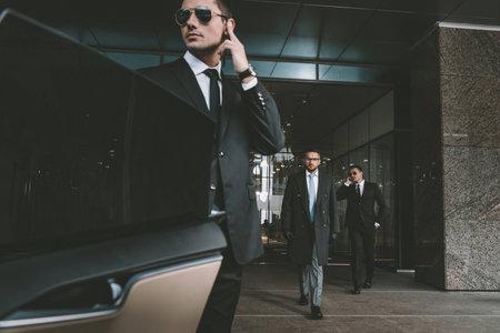guardia del corpo che apre la portiera della macchina per uomo d'affari Archivio Fotografico