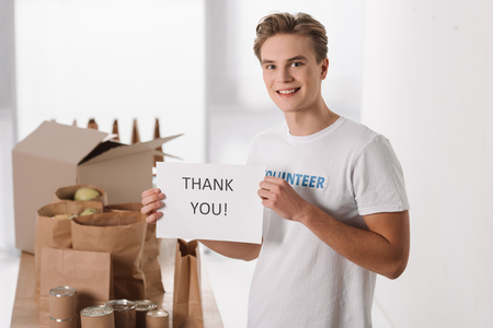 young volunteer with thank you placard in hands Standard-Bild - 104555937