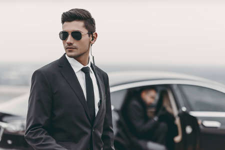bodyguard reviewing territory while businessman going out from car Archivio Fotografico