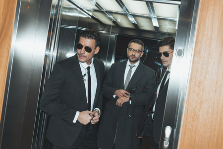 bodyguards looking out from elevator and businessman looking at watch