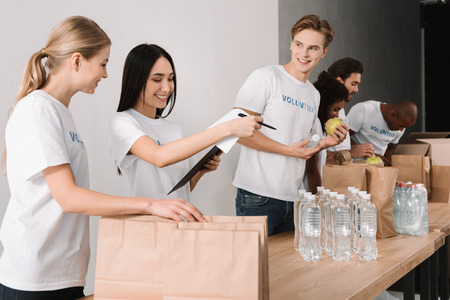 multiethnic young group of volunteers packing food for charity Zdjęcie Seryjne