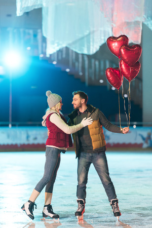 beautiful happy young couple with heart shaped balloons smiling each other on rink Banque d'images - 104556144