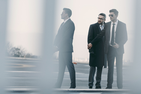 view through fence of bodyguards protecting businessman on helipad Stock Photo