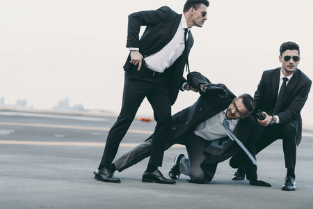 two bodyguards in sunglasses protecting falling businessman Stock Photo