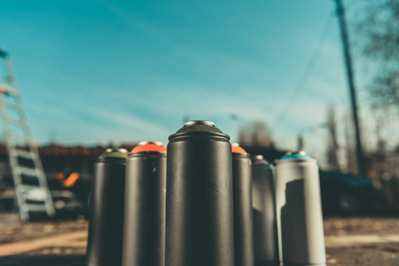 cans with colorful spray paint for graffiti on asphalt with blue sky on background
