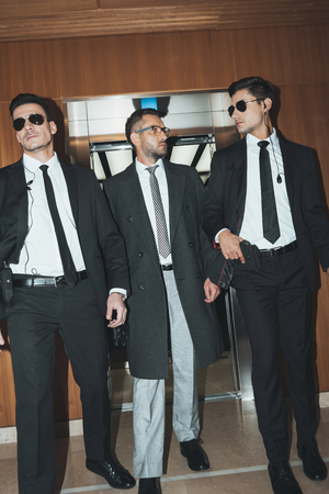 bodyguards and businessman walking from elevator in business center