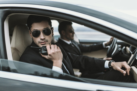 bodyguard in sunglasses talking by portable radio while sitting in car
