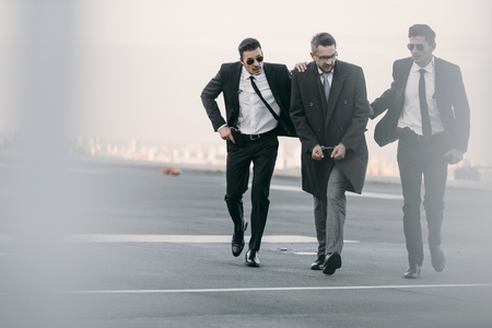 security guards going with arrested man on helipad Stock Photo