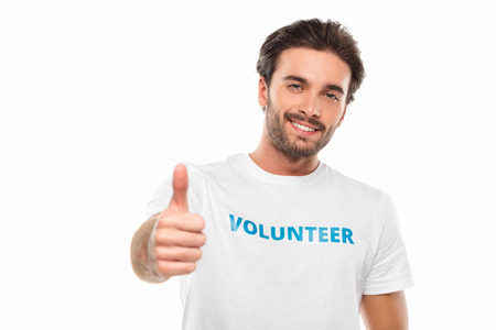 handsome young volunteer showing thumb up isolated on white Standard-Bild - 104556300