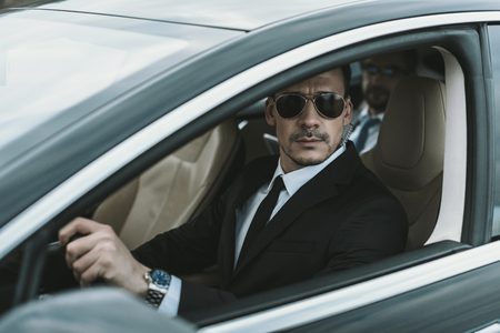 bodyguard sitting in car with businessman and looking away Stock Photo
