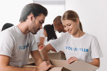 young happy volunteers packing goods in box for charity