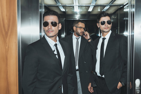 bodyguards reviewing territory when businessman talking by smartphone in elevator