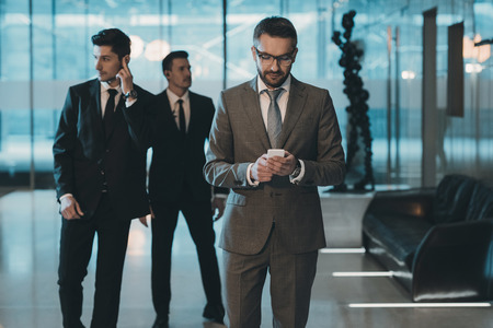 handsome businessman in glasses standing and looking at smartphone