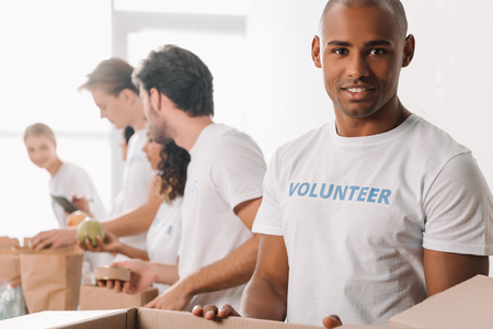 handsome african american volunteer with cardboard box and blurred colleagues working on background Standard-Bild - 104556078