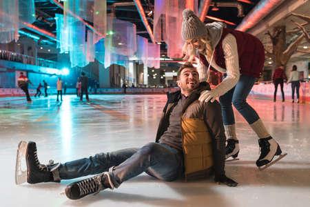 Hermosa joven pareja sonriente enseñando a patinar sobre hielo en la pista