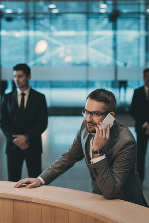 businessman standing at reception counter and talking by smartphone Stock Photo