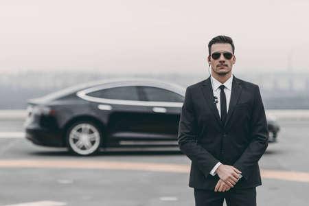 guardia del corpo seria in piedi con occhiali da sole e auricolare di sicurezza sull'eliporto